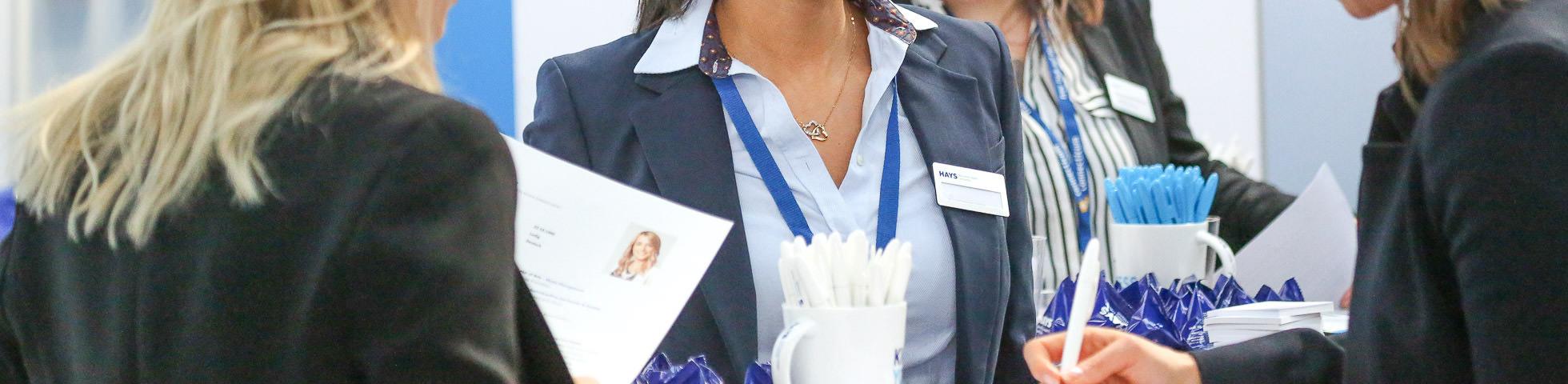 Foto eines Bewerbungsmappenchecks auf der Connecticum mit Mitarbeitern vom Employer Branding in der Halle