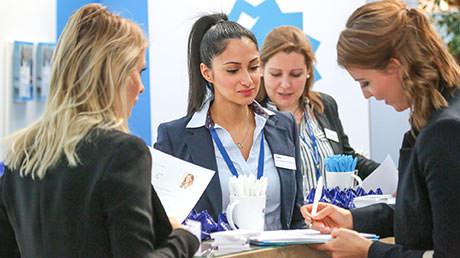 Foto und Bild eines Bewerbungsmappenchecks am Stand eines Unternehmens auf der Karrieremesse